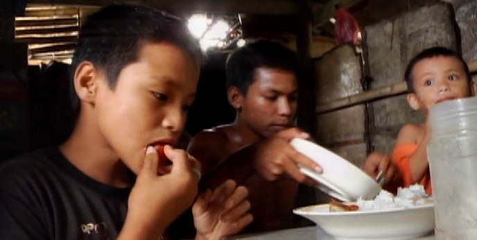 "Young ""coin divers,"" who dive for coins near the Allen port in Northern Samar, eat a hastily prepared rice porridge.  The International Rice Research Institute (IRRI)  based in the Philippines says it is trying to address the problem of malnutrition among the country's poor by developing iron-fortified rice varieties that will be ready for public distribution and consumption in 2029.  (Photo contributed by Rommel B. David)"