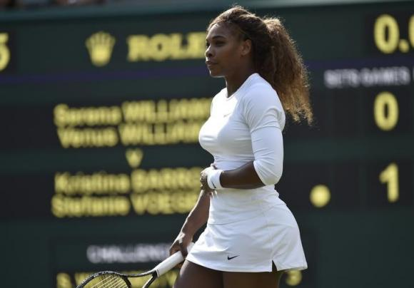 Serena Williams of the U.S. holds her stomach before retiring from her women's doubles tennis match with Venus Williams of the U.S. against Kristina Barrois of Germany and Stefanie Voegele of Switzerland at the Wimbledon Tennis Championships, in London July 1, 2014. CREDIT: REUTERS/TOBY MELVILLE