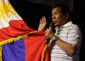 This photo taken on April 19, 2016 shows Rodrigo Duterte, front-runner presidential candidate for the May 9 elections, swearing in front of a national flag and supporters (not pictured) during a campaign sortie in Iloilo City, central Philippines.