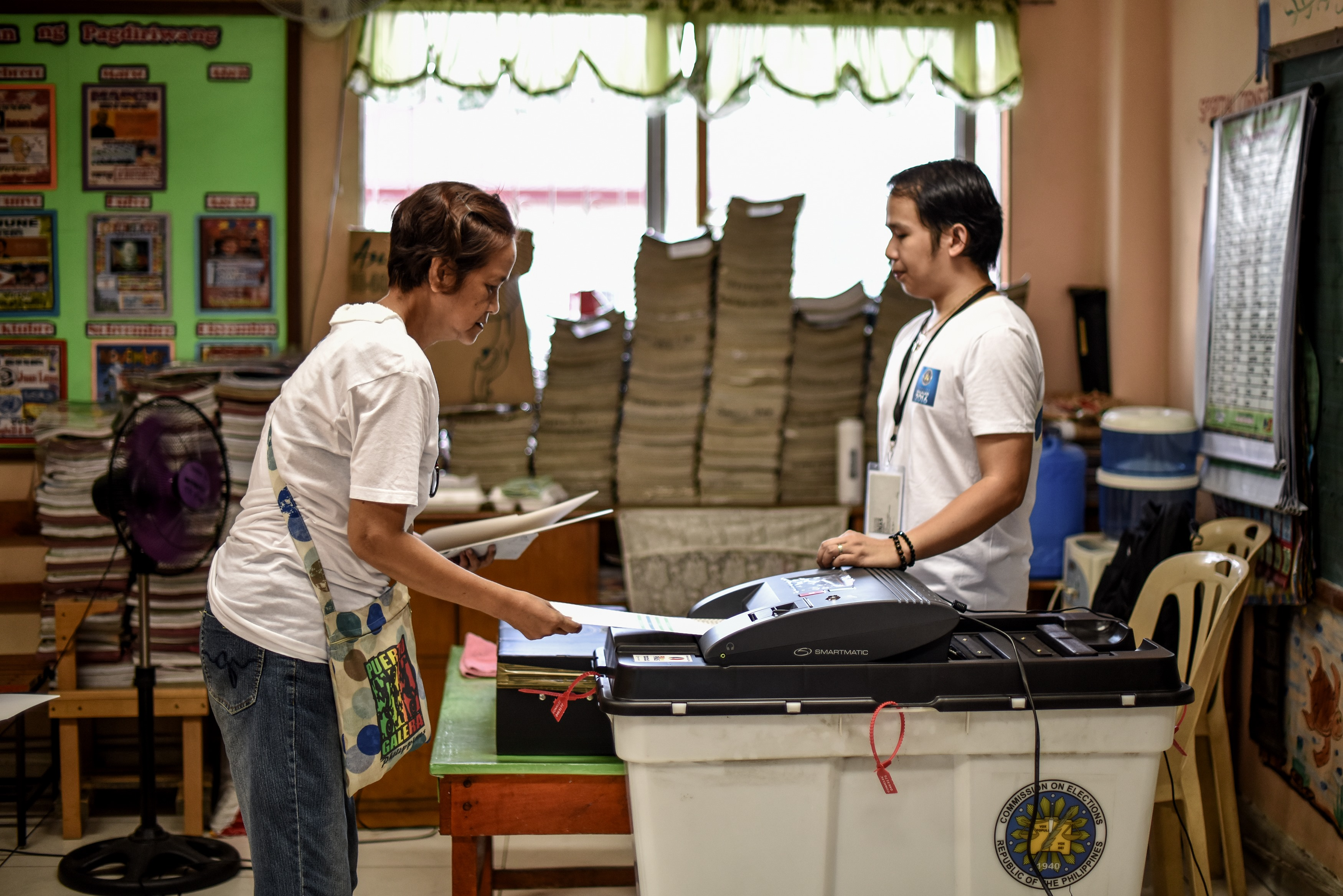 An elderly Filipino woman (L) places her ballot paper into a vote counting machine during the presidential and vice presidential elections at a polling center in Manila on May 9, 2016.  Voting was underway in the Philippines on May 9 to elect a new president, with anti-establishment firebrand Rodrigo Duterte the shock favourite after an incendiary campaign in which he vowed to butcher criminals. / AFP PHOTO / MOHD RASFAN