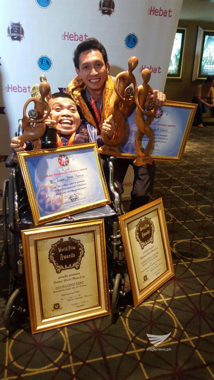 """Walang Take Two"" director Carlo Jay Ortega Cuevas and actor Dennis ""Oblax"" Garcia hold the awards and plaques received by the INCinema produced film at the World Film Awards in Jakarta, Indonesia. (Eagle News Service)"