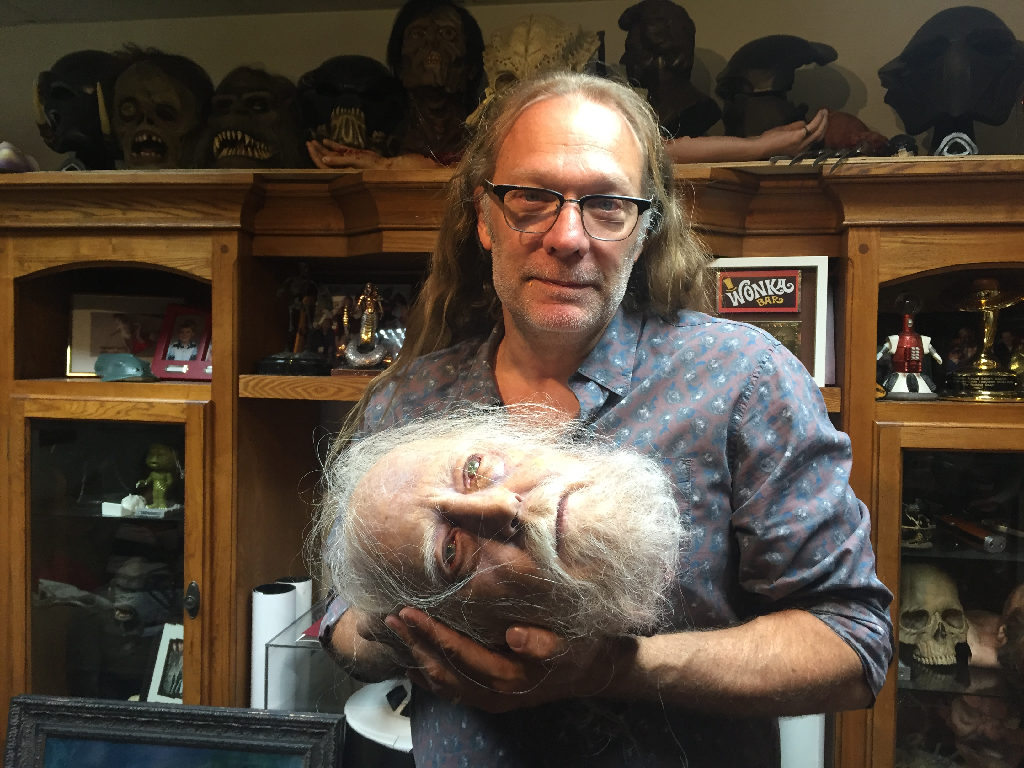 Special effects artist Greg Nicotero cradles the severed head of Hershel Greene, a character from AMC series 'The Walking Dead', as he poses for a photo at his studio KNB EFX in Chatsworth, California on June 8, 2016.  He is the God of Gore, the Sultan of Splatter, the Emperor of Entrails -- and the brains behind some of the most iconic blood and guts set-pieces in film history. If you've seen something in a violent movie that made the blood drain from your face, there's a good chance that Oscar-winning Greg Nicotero provided the special effects.  / AFP PHOTO / Frankie TAGGART