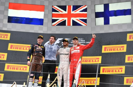 Mercedes AMG Petronas F1 Team's British driver Lewis Hamilton (2nd R) celebrates victory on the podium ahead of Infiniti Red Bull racing's Belgian-Dutch driver Max Verstappen (L) and Ferrari's Finnish driver Kimi Raikkonen (R) with Chief strategist AMG Mercedes Team James Vowles (2nd L) after the Formula One Grand Prix of Austria at the Red Bull Ring in Spielberg, Austria on July 3, 2016.   Mercedes AMG Petronas F1 Team's British driver Lewis Hamilton won the race ahead of Infiniti Red Bull racing's Belgian-Dutch driver Max Verstappen (2nd) and Ferrari's Finnish driver Kimi Raikkonen (3rd). / AFP PHOTO / ANDREJ ISAKOVIC