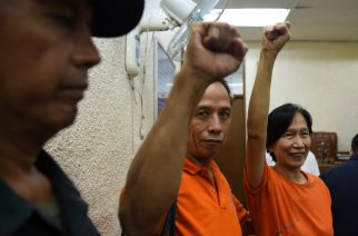 Philippines communist rebel leaders Benito Tiamzon's (C) and wife, Wilma (R) raise clinched fists while a policeman (L) looks on as they arrive for their bail hearing at a court in Manila on August 11, 2016.   Benito and Wilma Tiamzon are attending their bail hearing for their temporary release, as consultants of the Communist party peace negotiating panel, and will be attending the second round of talks between the government and communist party leaders in Oslo, Norway this month, as part of President Rodrigo Duterte's efforts to revive stalled peace talks, a step towards ending one of Asia's longest insurgencies that has killed tens of thousands of people. / AFP PHOTO / TED ALJIBE