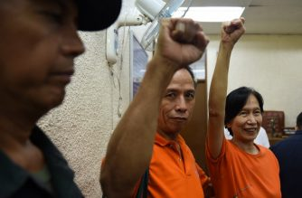 Communist rebel leaders Benito Tiamzon's (C) and wife, Wilma (R) raise clinched fists while a policeman (L) looks on as they arrive for their bail hearing at a court in Manila on August 11, 2016.   Benito and Wilma Tiamzon are attending their bail hearing for their temporary release, as consultants of the Communist party peace negotiating panel, and will be attending the second round of talks between the government and communist party leaders in Oslo, Norway this month, as part of President Rodrigo Duterte's efforts to revive stalled peace talks, a step towards ending one of Asia's longest insurgencies that has killed tens of thousands of people. / AFP PHOTO / TED ALJIBE