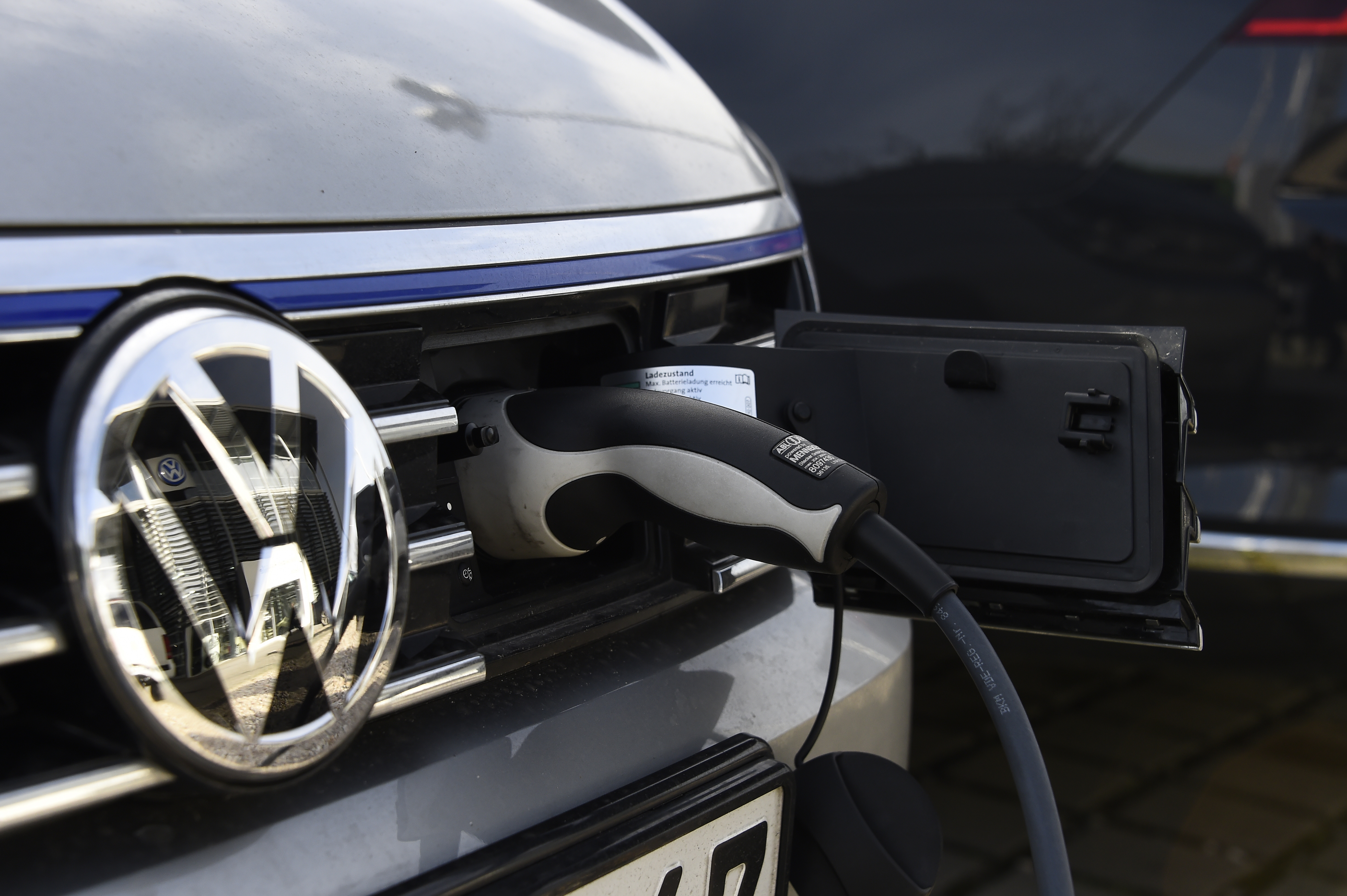 A VW electric car is plugged on a power station at a Service station in Berlin on February 2, 2016. / AFP PHOTO / TOBIAS SCHWARZ