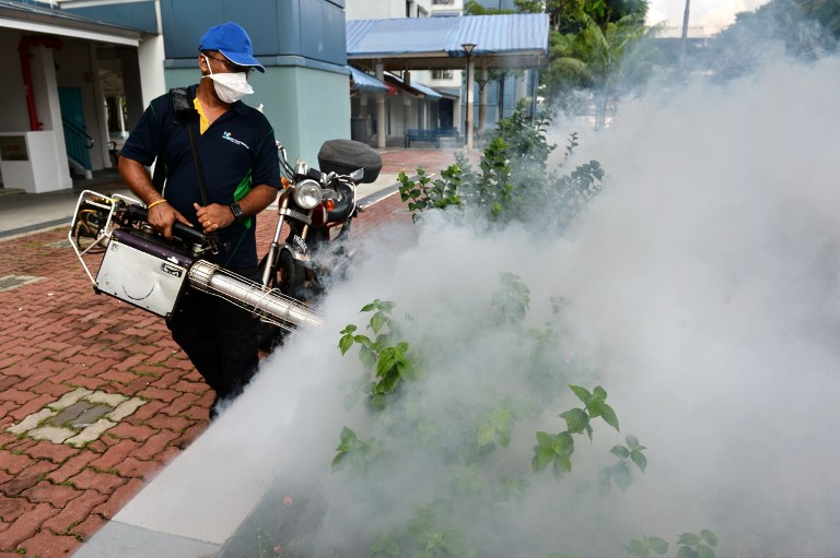 A pest control worker fumigates the grounds of a residential estate in the Bedok North area of Singapore on September 1, 2016. Singapore's Zika outbreak escalated September 1 after Malaysia said one of its citizens returned infected from the city-state as the government expanded its fumigation drive to a new area identified as a potential cluster for the virus. / AFP PHOTO / ROSLAN RAHMAN
