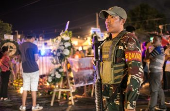 A military personnel stands guard as residents place flowers and lighted candles at a blast site in Davao City, in the southern island of Mindanao on September 4, 2016, as authorities tightened its security in public places two days after a bomb explosion at a night market that left 14 people dead and 60 wounded. Philippines police September 4 were searching for three people wanted for questioning over the bombing of a night market in President Rodrigo Duterte's hometown blamed on an Islamic militant group. / AFP PHOTO / MANMAN DEJETO