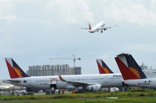 In this photo tatken on September 13, 2016 shows Philippine airlines planes are parked while another takes off at the international airport of Manila. / AFP PHOTO / TED ALJIBE