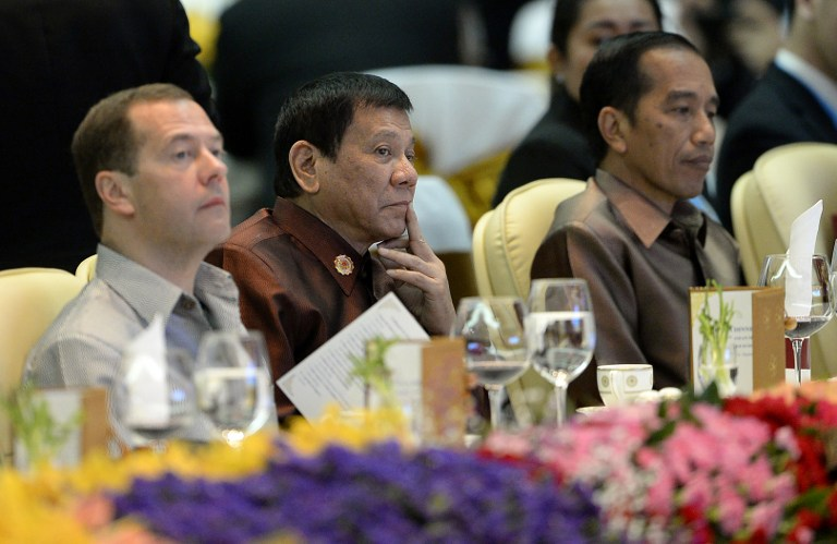 Philippine President Rodrigo Duterte (C) sits beside Russian Prime Minister Dmitry Medvedev (L) and Indonesia's President Joko Widodo at the gala dinner during the second day of the Association of Southeast Asian Nations (ASEAN) Summit in Vientiane on September 7, 2016. The gathering will see the 10 ASEAN members meet by themselves, then with leaders from the US, Japan, South Korea and China. / AFP PHOTO / NOEL CELIS