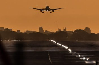 A passenger aircraft prepares to land during sunrise at London Heathrow Airport in west London on October 17, 2016. Britain's government is considering whether to approve a third runway at Heathrow or expand air capacity in southeast England at another airport such as London Gatwick. / AFP PHOTO / Daniel Leal-Olivas
