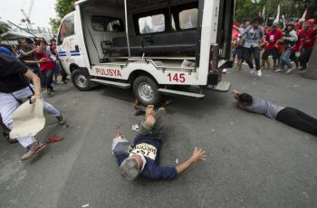 Protesters lie on the ground after being hit by a police van during a rally in front of the US embassy in Manila on October 19, 2016.  A Philippine police van on October 19 rammed and ran over baton-wielding protesters outside the US embassy in Manila. / AFP PHOTO / Rob Reyes