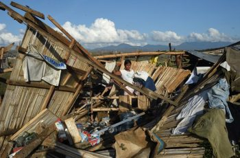 A resident removes dried clothes amongst the ruins of their house destroyed at the height of typhoon Haima in Cabagan town, Isabela province, north of Manila on October 21, 2016.  Hungry Philippine typhoon survivors huddled in makeshift shelters and waited for aid on October 21, after losing nearly everything from one of the most powerful storms to hit the Southeast Asian archipelago. / AFP PHOTO / TED ALJIBE