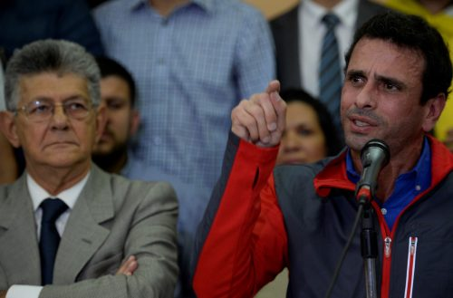 Venezuelan opposition leader Henrique Capriles speaks next to the president of the National Assembly, Henry Ramos Allup, during a press conference in Caracas on October 21, 2016. A furious Venezuelan opposition Friday vowed mass protests, accusing the Socialist government of staging a coup by blocking its drive for a recall referendum against President Nicolas Maduro. / AFP PHOTO / Federico PARRA