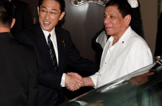 Philippines' President Rodrigo Duterte (R) is welcomed by Japanese Foreign Minister Fumio Kishida (L) prior to their dinner meeting at the entrance of a Japanese restaurant in Tokyo on October 25, 2016.  Duterte is in Japan on a three day visit. / AFP PHOTO / TOSHIFUMI KITAMURA