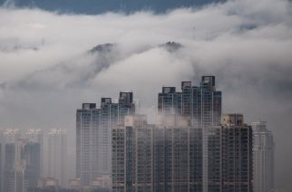 Low lying clouds descend upon buildings in the Kowloon district of Hong Kong on March 23, 2016.   / AFP PHOTO / Anthony WALLACE