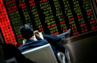 An investor reads a newspaper in front of a screen showing stock market movements at a securities company in Beijing on January 20, 2016. Asian markets resumed their downward spiral on January 20  with the previous day's China-fuelled rally effectively wiped out by ongoing worries about plunging oil prices and the state of the world economy.       AFP PHOTO / WANG ZHAO / AFP PHOTO / WANG ZHAO