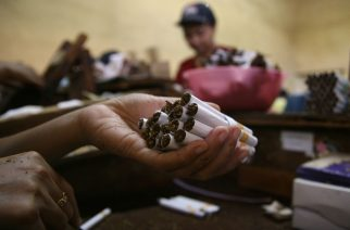 In this photograph taken on January 29, 2013 a person holds cigarettes in a local Indonesian tobacco company employing 600 women workers in Malang located in East Java province. Indonesian President Susilo Bambang Yudhono signed a tobacco regulation on December 24, 2012 in an effort to curb tobacco consumption which has faced staunch opposition from the cigarette lobby. More than 237,000 people work in the country's tobacco industry, producing some 190 billion cigarettes, according to data from the World Health Organization.  AFP PHOTO / AMAN ROCHMAN / AFP PHOTO / AMAN ROCHMAN