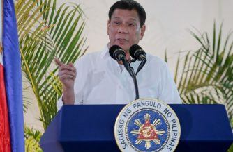 """Philippine President Rodrigo Duterte gestures as he delivers a speech, prior to his departure for the APEC summit in Peru, at Davo airport, in southern island of Mindanao on November 17, 2016. Duterte threatened on November 17 to do a Russia and pull his country out of the International Criminal Court, incensed at foreign criticism of alleged extrajudicial killings in his deadly drug war. Russia on November 16 formally withdrew its signature to the ICC's founding Rome Statute, calling the tribunal's work """"one-sided and inefficient"""".  / AFP PHOTO / MANMAN DEJETO"""