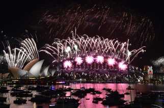 Fireworks light up the sky over Sydney's Opera House (L) and Harbour Bridge during New Year celebrations in Sydney on January 1, 2016.  AFP PHOTO / Saeed KHAN / AFP PHOTO / SAEED KHAN