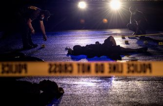This picture taken on October 29, 2016 shows police officers investigating a crime scene where two alleged drug dealers were gunned down by unidentified men in Manila. / AFP PHOTO / Noel CELIS