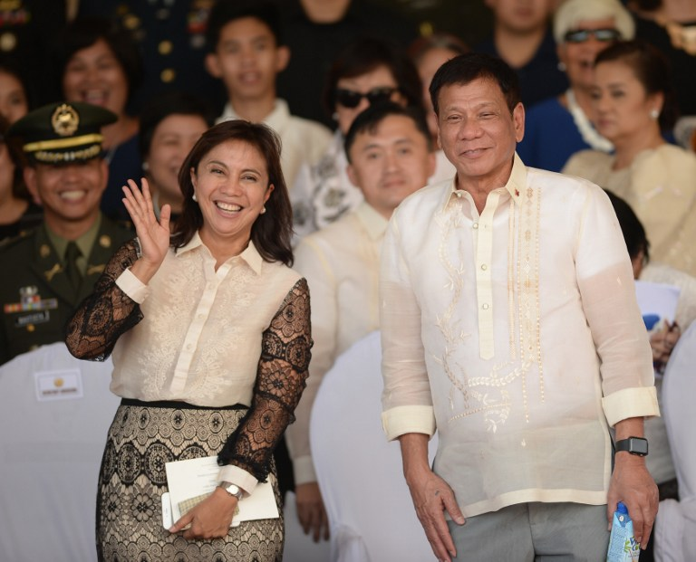 (FILES) This file photo taken on July 1, 2016 shows Philippines' President Rodrigo Duterte (R) posing for photographs with Vice-President Leni Robredo after the military parade at the military headquarters in Manila. Philippine Vice-President Leni Robredo said on December 4, 2016 she was told that President Rodrigo Duterte had barred her from cabinet meetings, and alleged there was a plot to oust her as his deputy. / AFP PHOTO / Ted ALJIBE