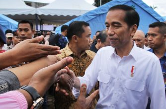 Indonesian President Joko Widodo (R) shakes hands with quake survivors at one of temporary shelter in Pidie Jaya, Aceh province, on December 9, 2016 during his two-day visit.  Widodo pledged to help the people of Aceh rebuild as he toured areas worst-hit by a devastating earthquake that killed more than 100 people and left thousands homeless. / AFP PHOTO / GATHA GINTING