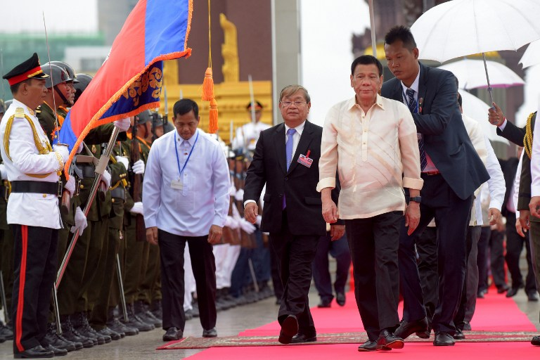 Philippines' President Rodrigo Duterte (2nd R) walks with Cambodia's Minister of Information Khieu Kanharith (3rd R) after paying respect to a statue of the late king Norodom Sihanouk in Phnom Penh on December 14, 2016. Duterte is on a two-day state visit to Cambodia. / AFP PHOTO / TANG CHHIN Sothy