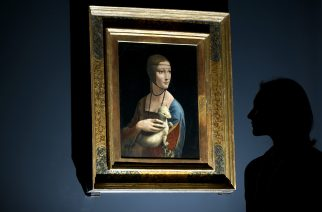 (FILES) This file photo taken on November 7, 2011 shows a woman posing for pictures beside a painting entitled 'Portrait of Cecilia Gallerani' (The Lady with an Ermine) by Italian artist Leonardo da Vinci during a photocall at the National Gallery in London. As it was confirmed on December 13, 2016, the Polish State would like to buy back the famous painting from the Czartoryski princes' family. / AFP PHOTO / CARL COURT / RESTRICTED TO EDITORIAL USE - MANDATORY MENTION OF THE ARTIST UPON PUBLICATION - TO ILLUSTRATE THE NEWS AS SPECIFIED IN THE CAPTION