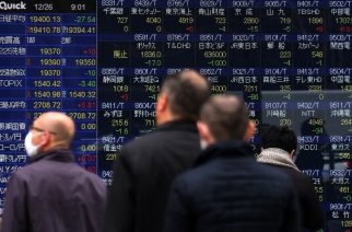 Pedestrians walk in front of an electronic board displaying stock prices on the Tokyo Stock Exchange in Tokyo on December 26, 2016. / AFP PHOTO / KAZUHIRO NOGI