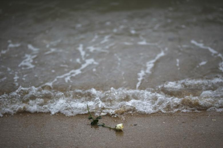 A rose is seen on the beach after being released by Thai children near a wave-shaped tsunami monument for victims of the 2004 tsunami in Ban Nam Khem, a southern fishing village destroyed by the wave December 26, 2014. REUTERS/Athit Perawongmetha