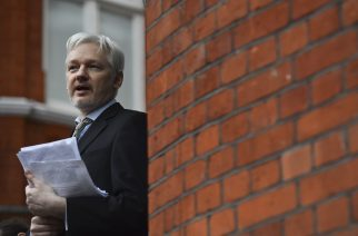 (FILES): This file picture taken on February 5, 2016 shows WikiLeaks founder Julian Assange addressing the media and holding a printed report of the judgement of the UN's Working Group on Arbitrary Detention on his case from the balcony of the Ecuadorian Embassy in central London. Accusations that Russia interfered with the US presidential election by leaking hacked documents via WikiLeaks have put a fresh spotlight on the crusading website's founder Julian Assange. / AFP PHOTO / BEN STANSALL