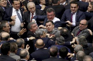 Ruling Justice and Development Party and main opposition Republican People's Party lawmakers scuffle at the parliament in Ankara during deliberations over a controversial 18-article bill to change the constitution to create an executive presidency January 11, 2017. Turkish lawmakers on Thursday approved three more articles in a hugely controversial bill bolstering the powers of President Recep Tayyip Erdogan, as lawmakers brawled and threw objects in a session of high tension. A brawl erupted in the chamber as the voting took place in an overnight session, with lawmakers punching each another and chairs being thrown, television pictures showed.  / AFP PHOTO / Adem ALTAN