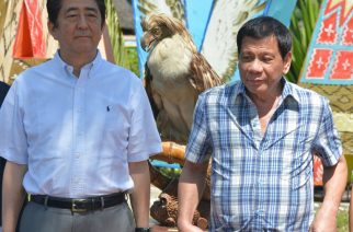 Japanese Prime Minister Shinzo Abe (L) and Philippine President Rodrigo Duterte stand next to a stuffed Philippine eagle during the naming of eagle ceremony in Davao city in southern island of Mindnao on January 13, 2017.   Abe arrived in the Philippines on January 12, becoming the first foreign leader to visit since President Rodrigo Duterte took office last year. / AFP PHOTO / TED ALJIBE