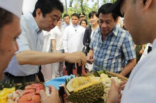 In this photograph released by the Presidential Office on January 13, 2017, Japanese Prime Minister Shinzo Abe (L) eats durian fruit with Philippine President Rodrigo Duterte (R) after attending various events in Davao City on the southern island of Mindanao.  Duterte gave visiting Abe a cozy taste of his southern home town on January 13, shunning stiff ceremonies for breakfast in his house as well as durian diplomacy. / AFP PHOTO / Presidential Office / SIMEON CELI