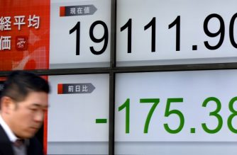 A businessman walks past an electric quotation board flashing the Nikkei key index of the Tokyo Stock Exchange (TSE) in front of a securities company in Tokyo on January 16, 2017.  Tokyo shares fell January 16 morning as automakers and other exporters were hit by a stronger yen, while the pound tumbled on reports Britain may be headed for a clean break with the EU. Tokyo's benchmark Nikkei index was down 0.91 percent, or 175.38 points, at 19,111.90 by the lunch break.  / AFP PHOTO / TORU YAMANAKA