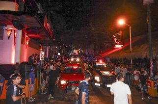 People remain in the street outside the Blue Parrot nightclub as firefighters and police agents patrol the area in Playa del Carmen, Quintana Roo state, Mexico where 5 people were killed, three of them foreigners, during a music festival on January 16, 2017.  A shooting erupted at an electronic music festival in the Mexican resort of Playa del Carmen early Monday, leaving at least five people dead and sparking a stampede, the mayor said. Fifteen people were injured, some in the stampede, after at least one shooter opened fire before dawn at the Blue Parrot nightclub during the BPM festival. / AFP PHOTO / VICTOR VARGAS / MAXIMUM QUALITY AVAILABLE