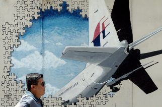 (FILES) This file picture taken on March 8, 2016 shows a man walking in front of a mural of missing Malaysia Airlines MH370 plane in a back-alley in Shah Alam.  The deep ocean hunt for missing passenger jet MH370 has been suspended after nearly three years without result, the Australian, Malaysian and Chinese governments said on January 17, 2017. / AFP PHOTO / MANAN VATSYAYANA