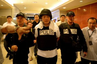 Police officer Ricky Sta. Isabel (C), one of the suspects in the kidnapping and murder of South Korean businessman Jee Ick Joo, is escorted by fellow policemen as they leave the National Bureau of Investigation (NBI) building in Manila on January 20, 2016.  A South Korean businessman kidnapped by Philippine policemen under the guise of a raid on illegal drugs was murdered at the national police headquarters in Manila, authorities said Thursday. / AFP PHOTO / NOEL CELIS