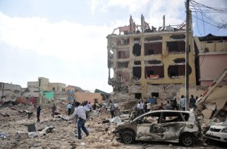 People react and walk among rubbles following an attack outside an hotel on January 25, 2017, in Mogadishu. At least seven people were killed after two car bombs exploded outside a popular Mogadishu hotel and gunmen forced their way inside the building and opened fire, police said. The attack, claimed by the Al-Qaeda aligned Shabaab insurgent group, began when a car loaded with explosives rammed the gate of the Dayah Hotel near the Somali parliament and state house. Gunmen then stormed the hotel and exchanged fire with security guards, according to police official Ibrahim Mohammed. / AFP PHOTO / MOHAMED ABDIWAHAB