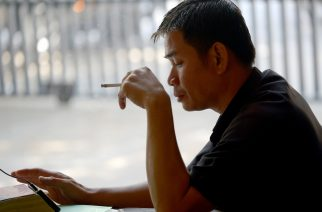 A Cambodian man smokes a cigarette as he plays with his smartphone in Phnom Penh on January 31, 2017. Smoking cost the world economy more than 1.4 trillion USD in 2012, and sucked up a twentieth of health care spending, a study said on January 31. / AFP PHOTO / TANG CHHIN SOTHY