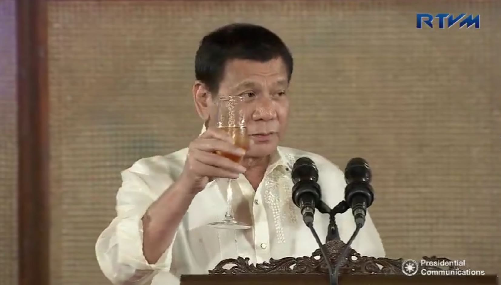 """""""Kampai! Bottoms up,"""" says President Duterte as he makes a toast after addressing the members of the international community, including the diplomatic corps, during his first hosting of the annual Vin d'Honneur at the Rizal Hall in Malacanang. (Photo grabbed from RTVM video)"""