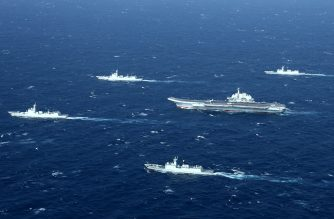 This aerial photo taken on January 2, 2017 shows a Chinese navy formation, including the aircraft carrier Liaoning (C), during military drills in the South China Sea. The aircraft carrier is one of the latest steps in the years-long build-up of China's military, as Beijing seeks greater global power to match its economic might and asserts itself more aggressively in its own backyard.  / AFP PHOTO / STR / China OUT