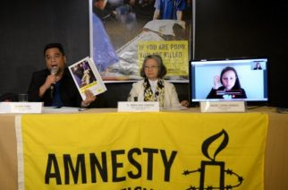 Wilnor Papa, from Amnesty International Philippines, shows a copy of their report during a press conference in Manila on February 1, 2017. Philippine police may have committed crimes against humanity by killing thousands of alleged drug offenders or paying others to murder as part of President Rodrigo Duterte's drug war, Amnesty International said February 1. TED ALJIBE / AFP