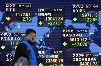 (FILES) This file photo taken on January 31, 2017 shows  Pedestrians walk in front of an electric quotation board flashing share prices of the world, including the Nikkei key index of the Tokyo Stock Exchange (top C), in Tokyo on January 31, 2017.  Asian markets edged down as dealers moved cautiously on February 3, 2017 following another tepid lead from Wall Street while focus shifts to the release later in the day of US jobs figures. / AFP PHOTO / Kazuhiro NOGI
