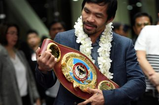 (FILES) This file photo taken on November 8, 2016 shows Philippine boxing icon Manny Pacquiao holding up his welterweight title upon his arrival at the airport in Manila. Manny Pacquiao on February 13, 2017 asked his legions of Twitter followers to choose his opponent after announcing his next world title defence will be in the United Arab Emirates. / AFP PHOTO / Ted ALJIBE