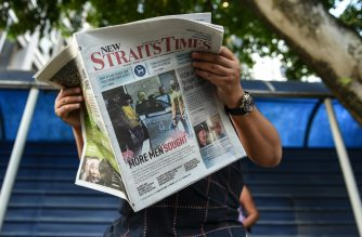 A journalist reads a newspaper with reports about the killed of North Korean man suspected to be Kim Jong-Nam, half-brother of North Korean leader Kim Jong-Un outside the Forensic department at Kuala Lumpur Hospital in Kuala Lumpur on February 17, 2017.   Malaysia will return the body of the half-brother of North Korea's leader, the country's deputy prime minister said on February 16, as police probing the airport assassination arrested a second woman. / AFP PHOTO / MOHD RASFAN