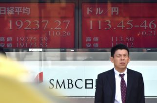 A pedestrian stands in front of an electric quotation board flashing the Nikkei key index of the Tokyo Stock Exchange (L) and the current exchange rate of the Japanese yen against the US dollar (R) in Tokyo on February 17, 2017.  Sharp jumped 2.17 percent to 329 yen after the company slashed its net loss estimate by more than a quarter to 27 billion yen ($238 million) for the year to March, citing lower materials costs. / AFP PHOTO / KAZUHIRO NOGI