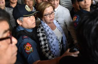 Philippine Senator Leila De Lima (C), a top critic of President Rodrigo Duterte, is escorted by police officers and her lawyer Alex Padilla (R, in white long sleeves) after her arrest at the Senate in Manila on February 24, 2017. / AFP PHOTO / TED ALJIBE