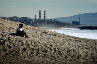 A woman sits on a sand berm created by city workers to protect houses from El Nino storms and high tides at Playa Del Rey beach in Los Angeles, California on November 30, 2015, at the start of the COP21 conference in Paris. Some 150 leaders, including US President Barack Obama, China's Xi Jinping, India's Narendra Modi and Russian President Vladimir Putin, will attend the start of the Paris conference, which is tasked with reaching the first truly universal climate pact, with the goal to limit average global warming to two degrees Celsius (3.6 degrees Fahrenheit), perhaps less, over pre-Industrial Revolution levels by curbing fossil fuel emissions blamed for climate change.       AFP PHOTO / MARK RALSTON / AFP PHOTO / MARK RALSTON